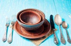 Todavía vida con la placa de cerámica rústica marrón y el viejo sistema de los cubiertos Imagen de archivo libre de regalías