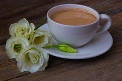 Todavía vida con la taza de café y de Eustoma de las flores en la parte posterior de madera Imagenes de archivo