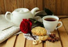 Todavía vida con la taza de té, de rosa del rojo y de galletas de harina de avena Fotografía de archivo libre de regalías