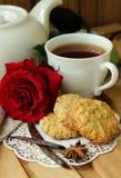 Todavía vida con la taza de té, de rosa del rojo y de galletas de harina de avena Imagenes de archivo