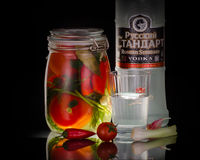 Todavía vida con la vodka rusa con los tomates adobados Fotografía de archivo