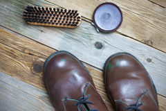 Todavía vida con las botas, el pulimento de zapato y el cepillo marrones fotografía de archivo