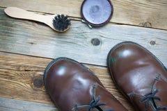 Todavía vida con las botas, el pulimento de zapato y el cepillo marrones del zapato fotos de archivo libres de regalías