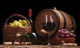Todavía vida con las botellas de vino, los vidrios y los barriles del roble Imagenes de archivo