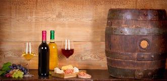 Todavía vida con las botellas y los vidrios de vino blanco rojo y con queso, el prosciutto y la uva en la bodega, barril de vino  Fotos de archivo libres de regalías