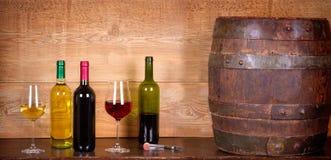Todavía vida con las botellas y los vidrios de vino blanco rojo y con queso, el prosciutto y la uva en la bodega, barril de vino  Fotos de archivo