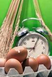 Todavía vida con las cáscaras de huevo y los huevos, despertador roto viejo, semilla del arroz de arroz, fondo verde Imagen de archivo libre de regalías