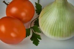 Todavía vida con las cebollas, los tomates amarillos y una hoja del perejil Fotos de archivo libres de regalías