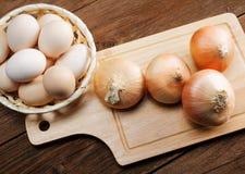 Todavía vida con las cebollas y los huevos de codornices Imagenes de archivo