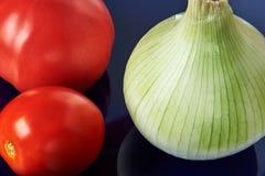 Todavía vida con las cebollas y los tomates rojos Fotografía de archivo libre de regalías