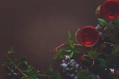 Todavía vida con las copas, las botellas, las uvas y las hojas Imagen de archivo