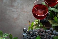 Todavía vida con las copas, las botellas, las uvas y las hojas Imágenes de archivo libres de regalías