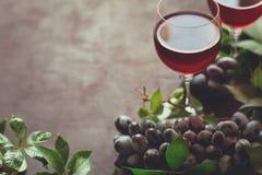 Todavía vida con las copas, las botellas, las uvas y las hojas Fotos de archivo