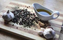 Todavía vida con las especias, el ajo, la pimienta y el aceite de oliva Imagen de archivo