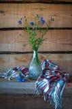Todavía vida con las flores azules en un florero de cristal y un sha hermoso Foto de archivo libre de regalías