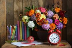 Todavía vida con las flores, el despertador, los libros y los lápices del otoño Fotografía de archivo