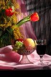 Todavía vida con las flores, el vino rojo y las frutas Imagen de archivo libre de regalías