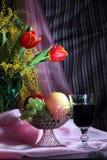 Todavía vida con las flores, el vino rojo y las frutas Imagenes de archivo