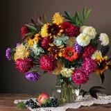 Todavía vida con las flores, la manzana y las bayas del otoño Imagenes de archivo