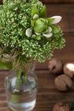 Todavía vida con las flores y el lirio verdes en un fondo de madera Imagenes de archivo