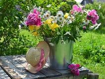 Todavía vida con las flores y el sombrero en la tabla vieja Fotos de archivo