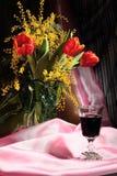 Todavía vida con las flores y el vino rojo Fotografía de archivo
