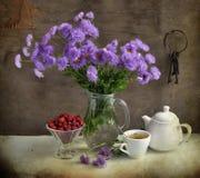Todavía vida con las flores y la fresa de la lila Foto de archivo