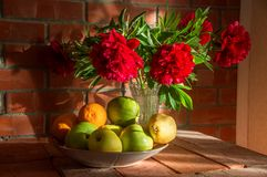 Todavía vida con las flores y la fruta contra una pared de ladrillo Imagen de archivo