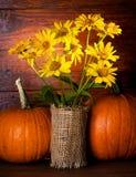 Todavía vida con las flores y las calabazas amarillas Imagen de archivo