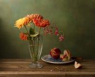 Todavía vida con las flores y los melocotones del crisantemo Foto de archivo