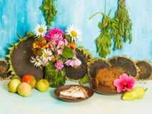 Todavía vida con las flores y los pasteles Fotos de archivo