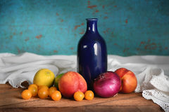 Todavía vida con las frutas y el florero azul Fotografía de archivo