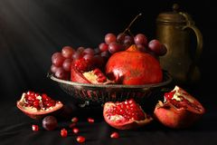 Todavía vida con las granadas, las uvas y la jarra de cobre amarillo Foto de archivo