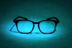 Todavía vida con las lentes de la lectura en fondo azul Fotos de archivo libres de regalías