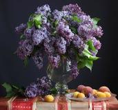 Todavía vida con las lilas en un florero y una fruta Imagen de archivo