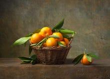 Todavía vida con las mandarinas en una cesta fotos de archivo