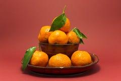 Todavía vida con las mandarinas frescas en un cuenco rojo Foto de archivo libre de regalías