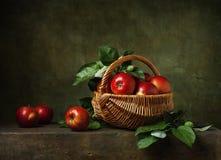 Todavía vida con las manzanas en cesta Foto de archivo