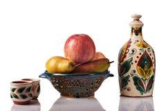 Todavía vida con las manzanas, peras, botella hecha a mano de cerámica, tazas Imagenes de archivo