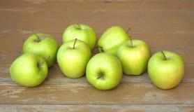 Todavía vida con las manzanas verdes en el primer marrón del fondo de la madera Imagen de archivo libre de regalías
