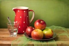 Todavía vida con las manzanas y el jarro rojos Imagen de archivo libre de regalías