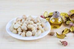 Todavía vida con las nueces de macadamia en la placa y la botella de aceite Fotos de archivo