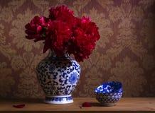 Todavía vida con las peonías de Borgoña en florero chino Imagenes de archivo