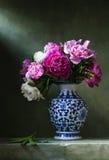 Todavía vida con las peonías en un florero chino fotografía de archivo