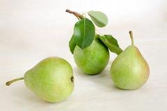Todavía vida con las peras Peras frescas verdes con las hojas en fondo ligero Imagen de archivo