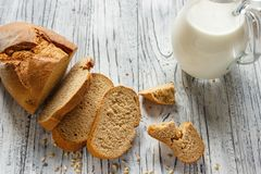 Todavía vida con las rebanadas de pan y de leche en un fondo de madera Fotos de archivo