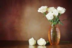 Todavía vida con las rosas blancas en el florero en una superficie de madera Foto de archivo