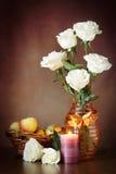 Todavía vida con las rosas blancas en el florero y una vela ardiente Fotos de archivo libres de regalías