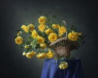 Todavía vida con las rosas salvajes del amarillo de la cesta foto de archivo