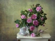 Todavía vida con las rosas salvajes del rosa de la cesta en la tabla de té foto de archivo libre de regalías